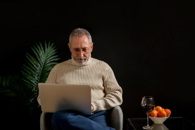 Elderly man browsing laptop near tangerines and wine