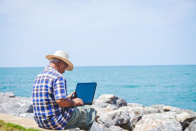 An elderly man carrying a laptop computer sitting at work by the sea