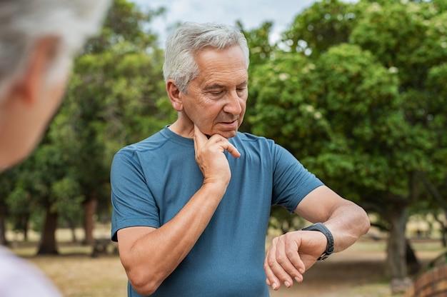 Пожилой мужчина проверяет пульс после бега