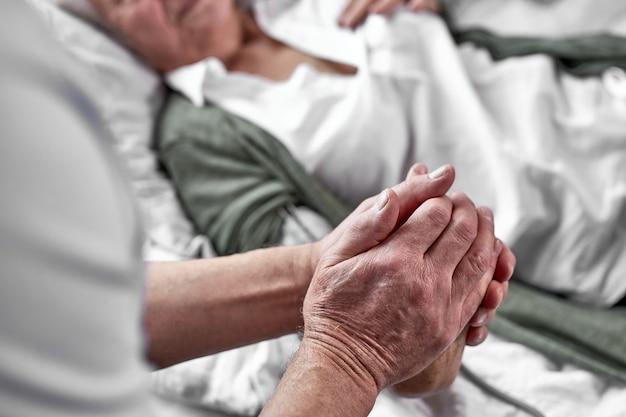 老人が妻の死を悼み、泣きながら横に座っている。手に焦点を当てます。コロナウイルス、covid-19コンセプト