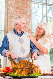 Elderly man cutting baked chicken at table near woman