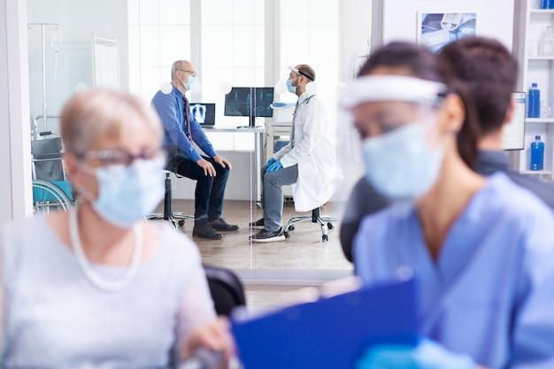 世界的大流行の際にコロナウイルスに対する防御を身に着けている病院の診察室で医師と話し合う老人