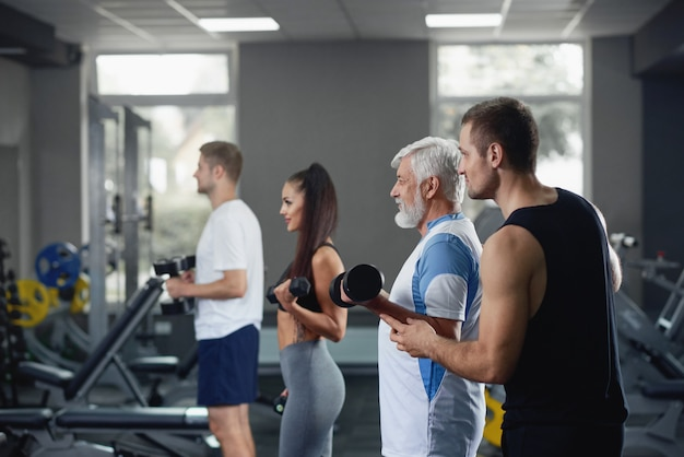 Elderly man doing exercise with group of younger people at gym.