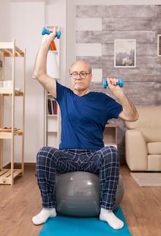 ダンベルを使用してパジャマでスポーツをしている老人