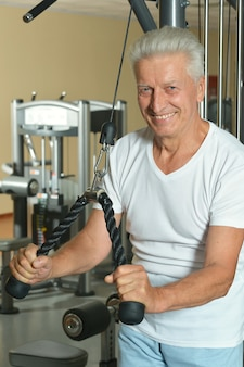 Elderly man doing sports in a gym