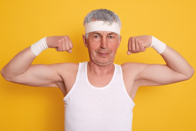 Elderly man dresses white headband showing his biceps and power,, posing against yellow wall after working out
