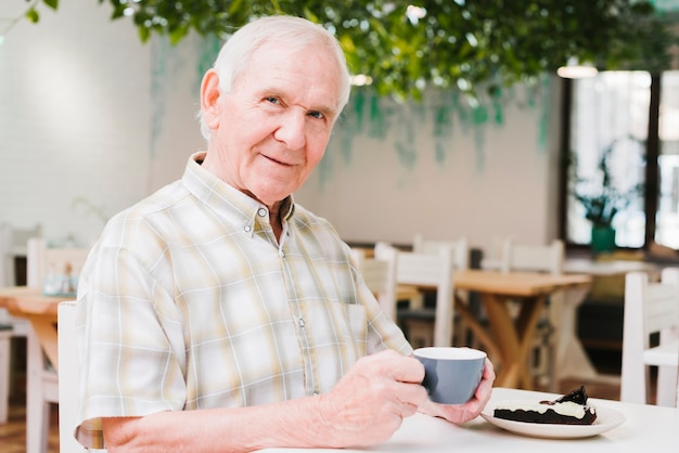 Elderly man drinking tea and looking at camera