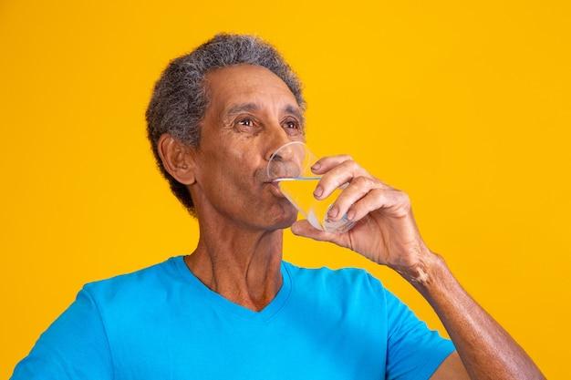 Elderly man drinking water to hydrate.