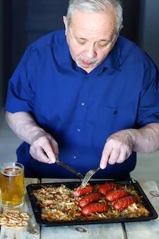 Пожилой мужчина ест сосиски и пьет пиво