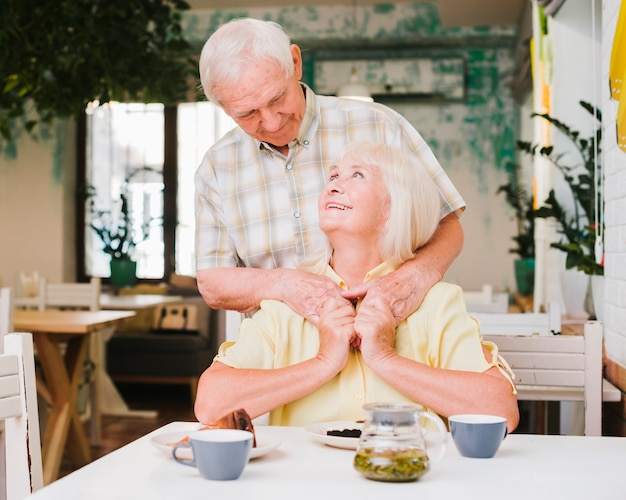 Elderly man embracing wife from behind