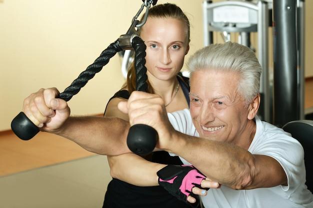트레이너와 함께 체육관에서 운동하는 노인