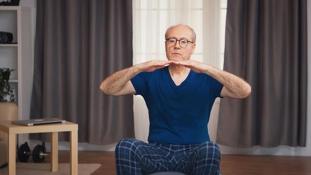 安定ボールに座って居間で運動している老人。老人年金受給者が自宅でヘルスケアスポーツを健康的に訓練し、高齢者でフィットネス活動を行う