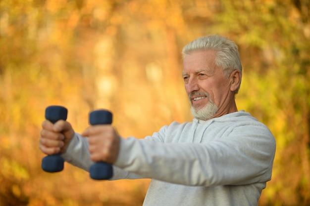 Elderly man exercising with dumbbells in autumn park