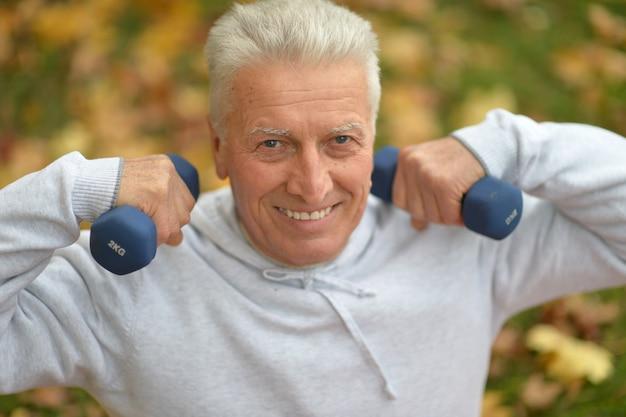 가을 공원에서 아령으로 운동하는 노인