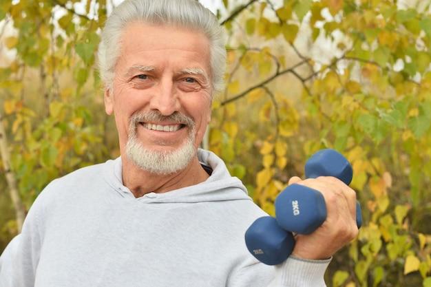 秋の公園でダンベルで運動する老人