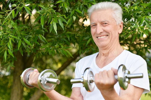 공원에서 아령으로 운동하는 노인