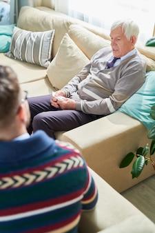 Elderly man explaining his feeling to psychiatrist