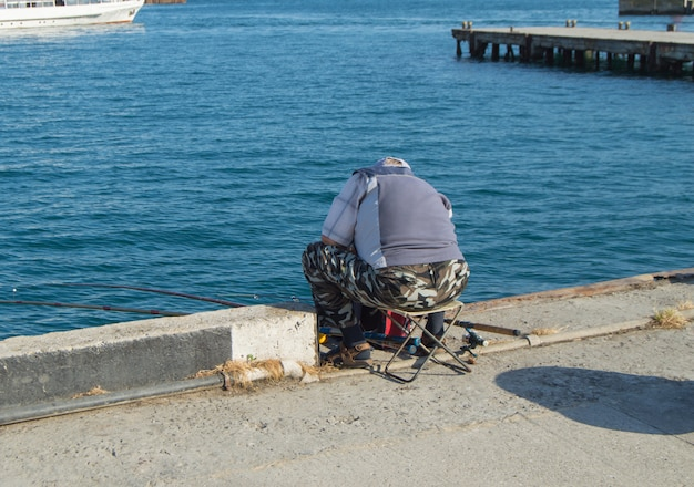 An elderly man fisherman sitting on a parapet by the sea and fishing on a fishing rod