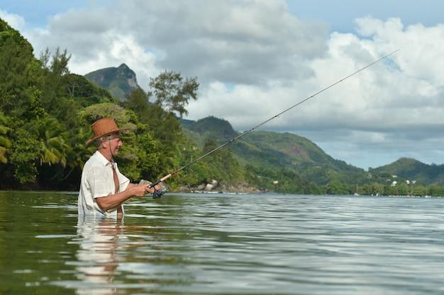 Пожилой мужчина ловит рыбу в море с удочкой