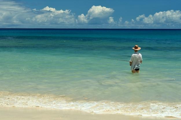 Пожилой мужчина, ловящий рыбу в море с удочкой