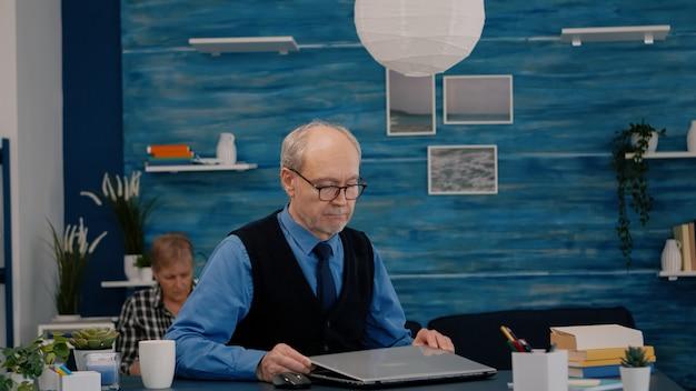 Пожилой мужчина-фрилансер открывает ноутбук, щурясь, читая электронную почту, работает из дома пенсионер и ...