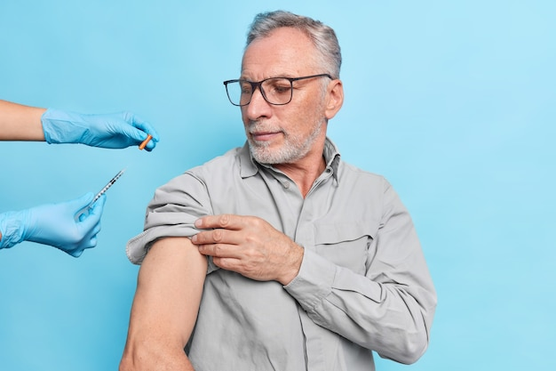 Elderly man gets vaccination against coronavirus looks attentively at syringe with vaccine wears eyeglasses
