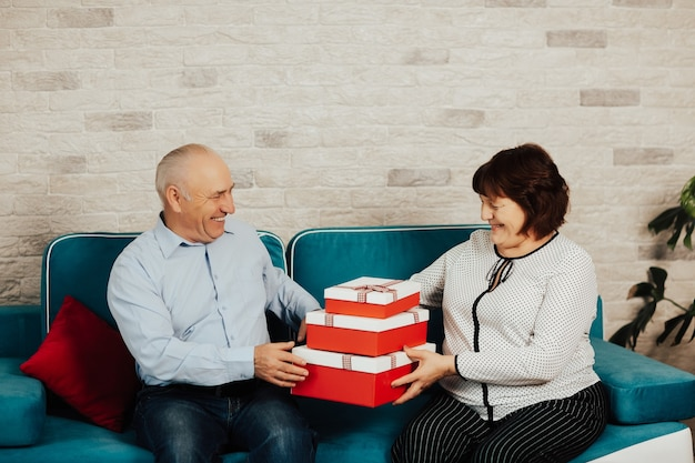 Elderly man giving present to his beloved wife at women day.