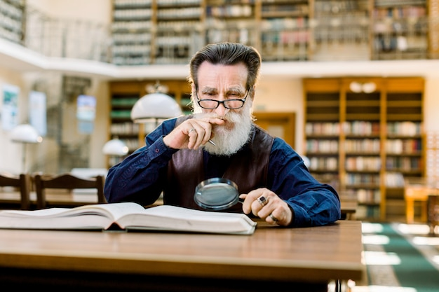 Elderly man in glasses sitting at the table in vintage library and thinking about the book he is reading, holding magnifying glass in hand