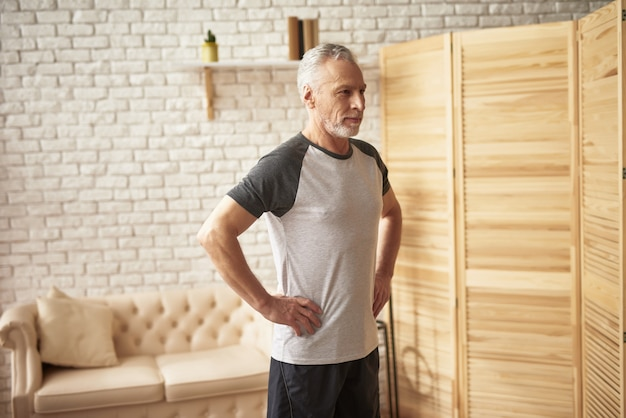 Elderly man good posture sport exercises at home.