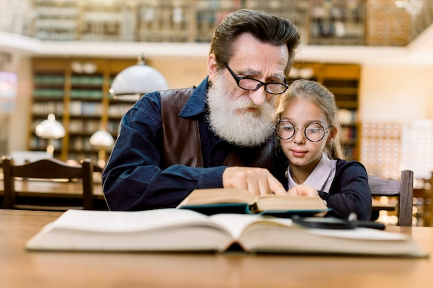 Elderly man grandfather and his granddaughter reading exciting book together while sitting in the library