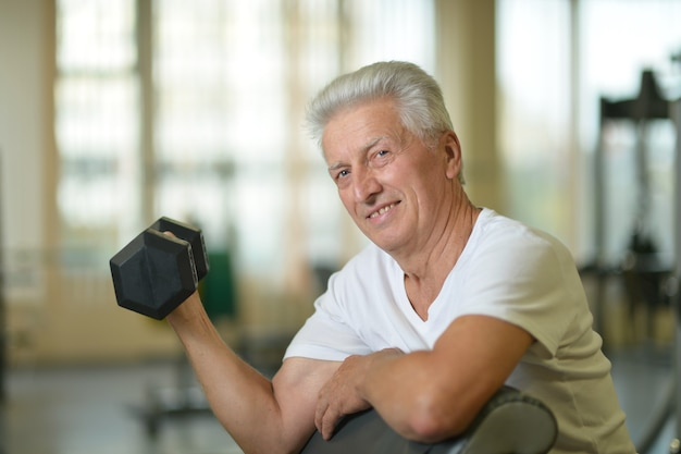 Elderly man in a gym. exercising with dumbbell