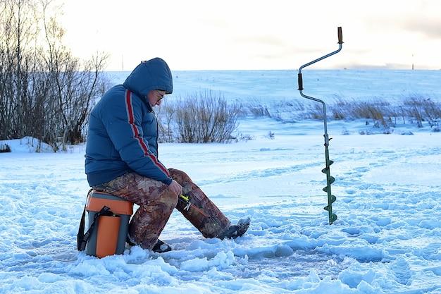 老人は冬に湖で釣りをしている