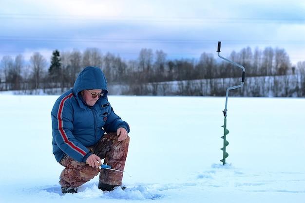 Пожилой мужчина ловил рыбу зимой на озере