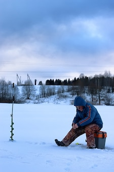 Elderly man has been fishing in the winter on the lake