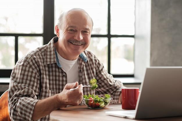 Elderly man having breakfast in front of a laptop