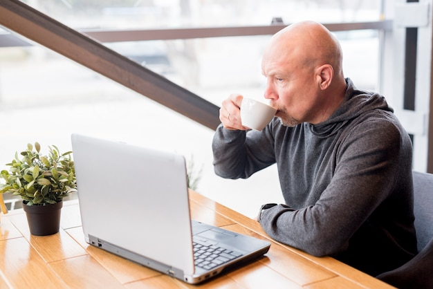 Elderly man having a coffee while uses the laptop