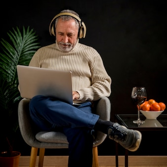 Elderly man in headphones watching movie on laptop