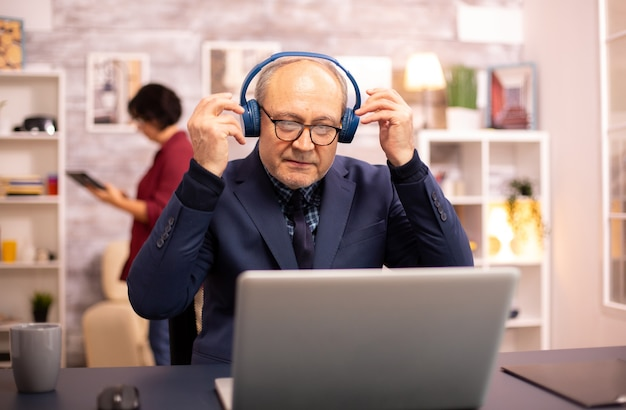 Elderly man in his 60s with headphones on his head listening to music and working on a modern laptop