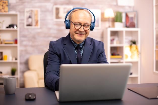 Uomo anziano sulla sessantina con le cuffie in testa che ascolta musica e lavora su un laptop moderno