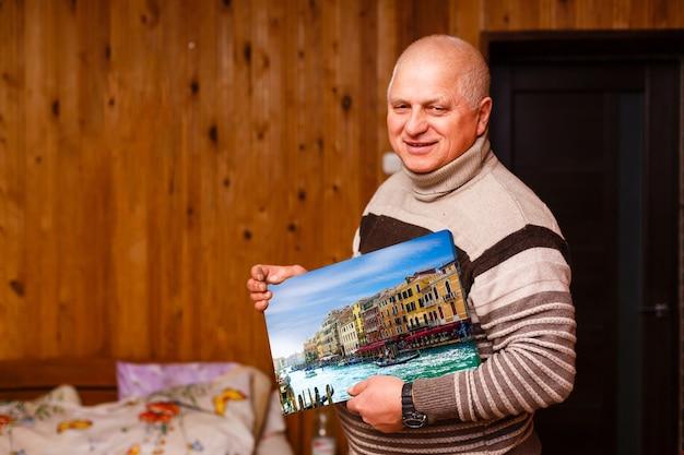 Пожилой мужчина держит фото холст в деревянном доме