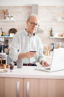 現代の支払いシステムを使用して、クレジットカードを保持している老人。年金受給者は、キッチンでの朝食時にクレジットカードとラップトップからのアプリケーションを使用してオンラインで支払います。インターネットを利用した定年退職者p