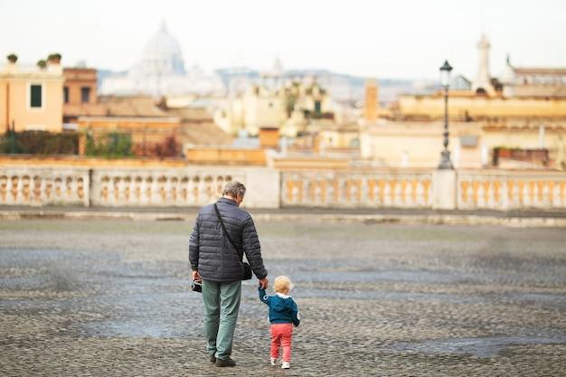 街で小さな孫娘の手を握っている老人