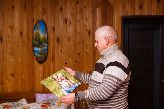 Elderly man holding a photo canvas in a wooden house