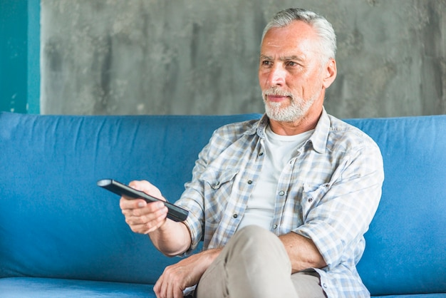 Elderly man holding remote control watching television