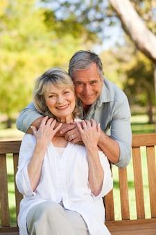Пожилой мужчина обнимает свою жену, которая находится на скамейке