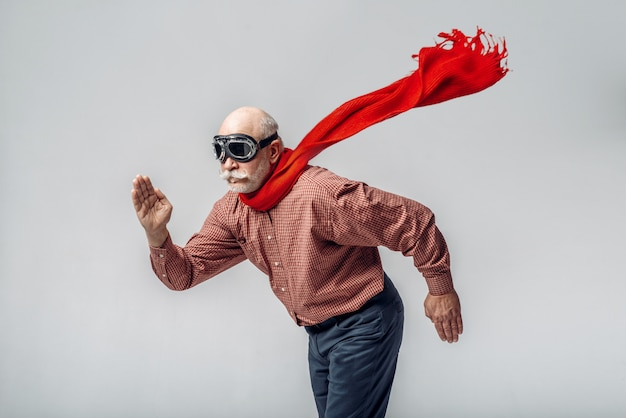 Пожилой мужчина в красном шарфе и пилотных очках