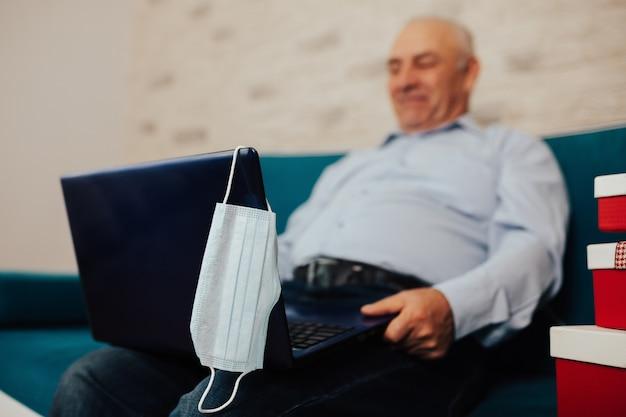 격리 기간 동안 집에서 거실에서 노트북으로 화상 통화를하는 파란색 셔츠에 노인