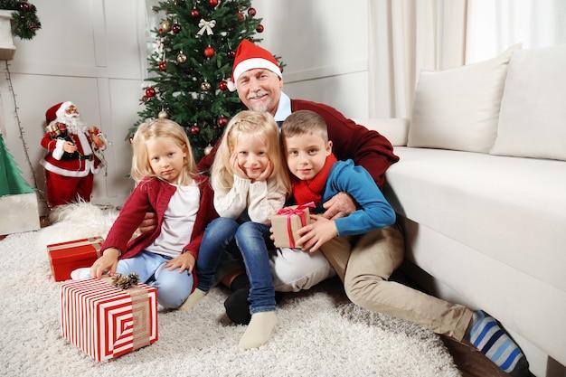 Пожилой мужчина в новогодней шапке с внуками дома