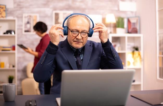 Пожилой мужчина 60 лет с наушниками на голове слушает музыку и работает на современном ноутбуке