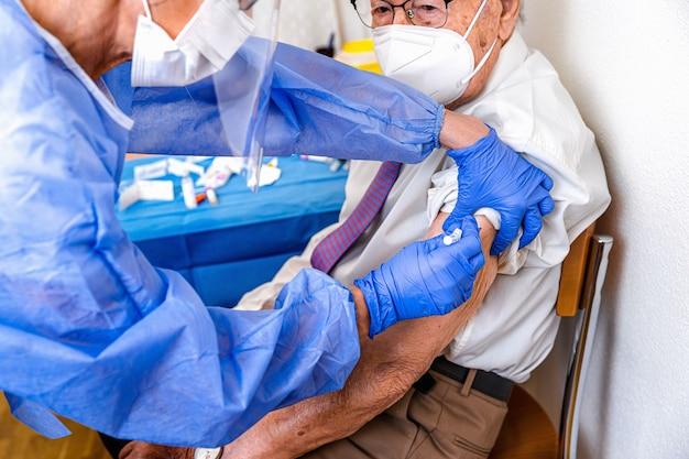 Пожилой мужчина в маске наблюдает, как медсестра в защитном костюме и маске covid делает ему вакцину от коронавируса
